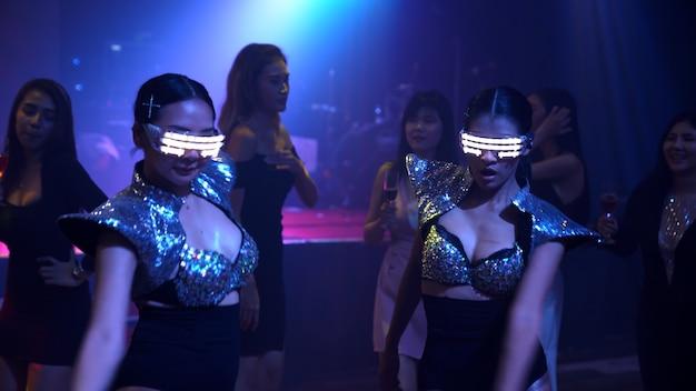 人々のグループがステージ上のdjからの音楽のビートに合わせてディスコナイトクラブで踊ります