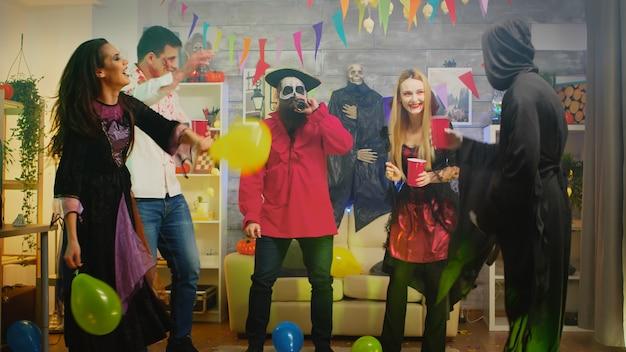 Группа людей танцует и веселится на вечеринке в честь хэллоуина в украшенном доме. повторить, зомби, ведьма и пират