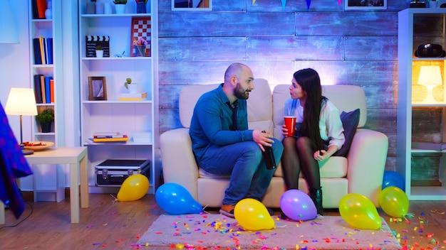 若いカップルが議論をしている間、アパートでネオンライトのあるパーティーで踊っている人々のグループ。