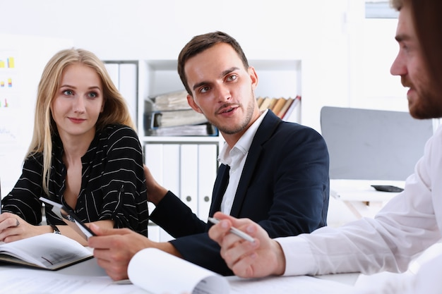 人々のグループはクリップボードパッドのクローズアップの問題について審議します。ホワイトカラー小切手マネーペーパー、証券取引所市場、収益リスト、パートナーシップ契約ディスカッションコンセプト