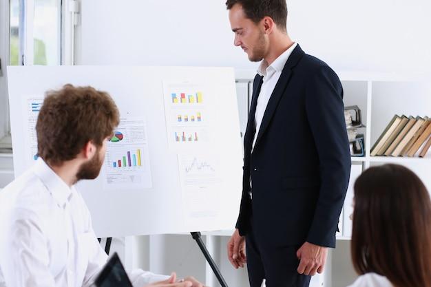 Группа людей обдумывает на белой доске