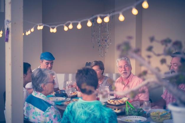 재미와 미소를 갖는 야외 테라스에서 집에서 함께 식사하는 사람들의 그룹