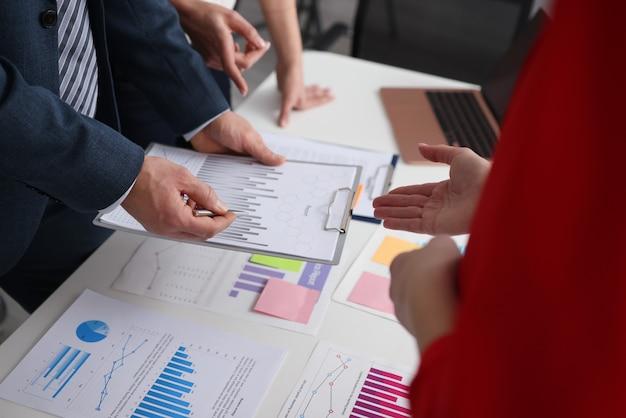 オフィスのクローズアップのドキュメントでチャートを議論している人々のグループ。ビジネスチームワークの概念