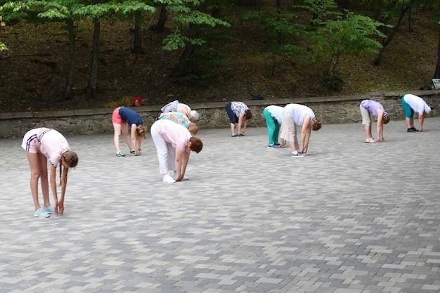 Группа людей, занимающихся йогой в парке. дыхательные упражнения на открытом воздухе.