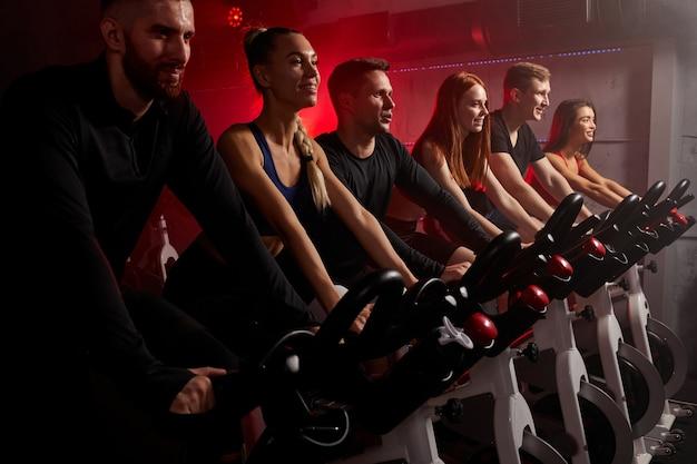 Группа людей, занимающихся велосимулятором в тренажерном зале, тренируется на велотренажере, изолирована в темном неоновом освещенном дымном пространстве. вид сбоку