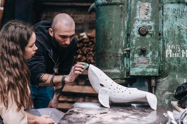 ワークショップで好きな仕事を楽しんでいる人々のグループ。人々はセラミッククジラに注意深く取り組んでいます