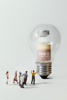 電球の光の中でコロナウイルスcovidワクチンに反対している人々のグループ(置物)。