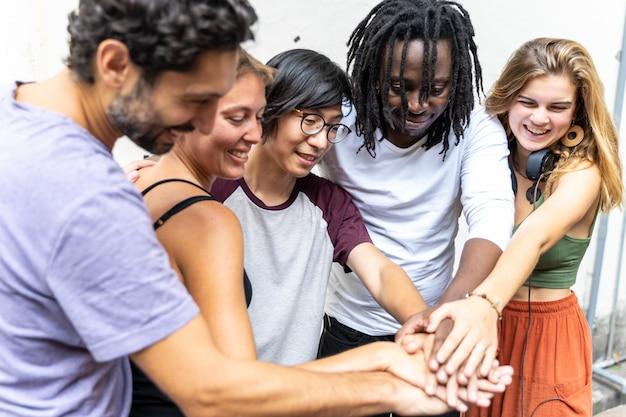 다른 인종 그룹에서 사람들의 그룹이 그들의 손을 모으기