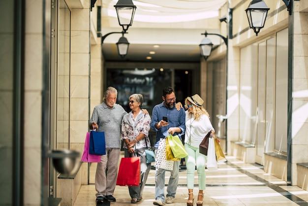 たくさんのバッグを腕に抱えて買い物に行き、モールや大きな店で手をつないでいる人々のグループ-家族はクリスマスの贈り物をすることと一緒に服を買うことを楽しんでいます