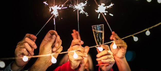 2021年の新年またはクリスマスを祝う夜に楽しんで楽しんでいる人々のグループ-白人の大人がスパークラーとグラスでシャンパンで踊る