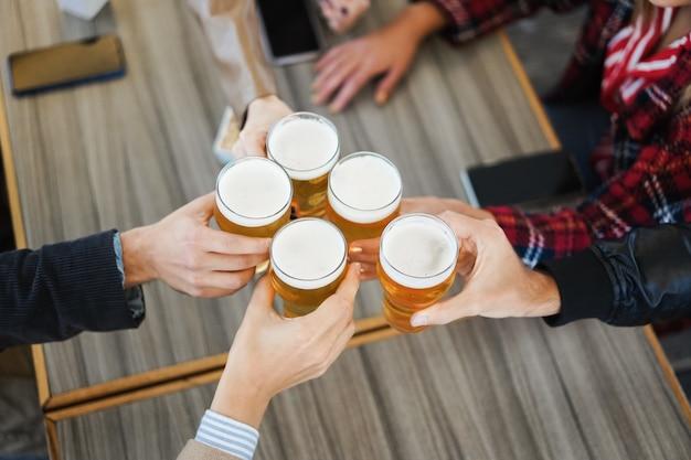 Группа людей, весело проводящих время с пивом в баре-пивоварне - фокус на очках