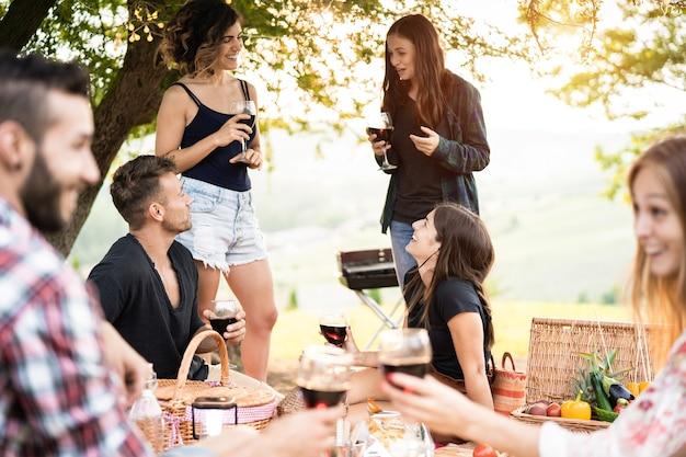 야외 피크닉 파티에서 와인을 먹고 마시는 재미를 가진 사람들의 그룹