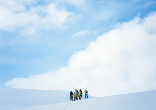 美しい青空の下で雪に覆われた山でハイキングする人々のグループ