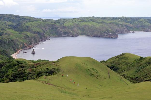 青空の下で緑に囲まれた海の周りの山をハイキングする人々のグループ
