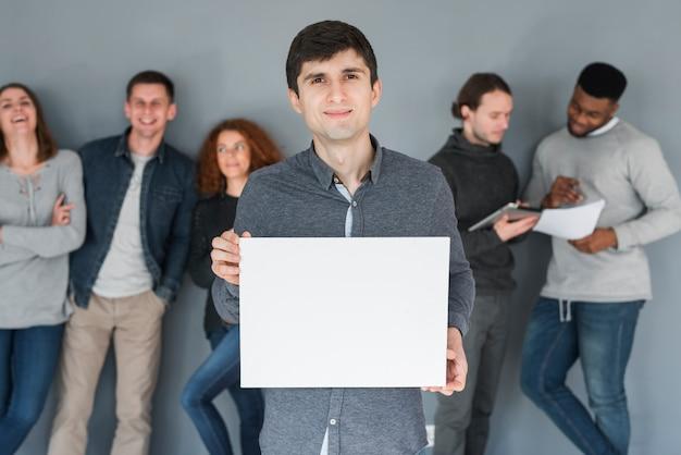 空白の紙のテンプレートを持っている人々のグループ