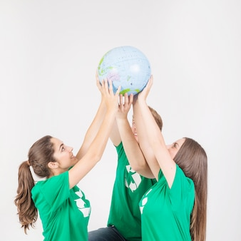 Группа людей, держащих земной шар над головой