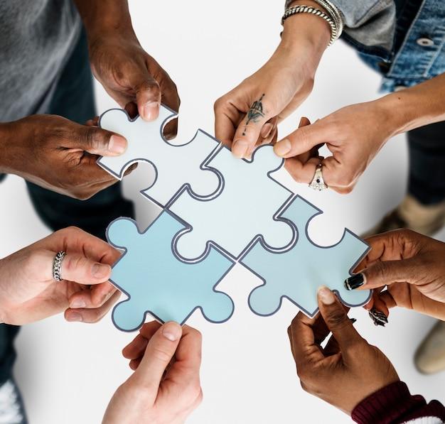 紙のジグソーパズルを保持している人々のグループ