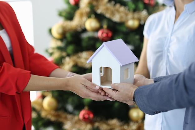 クリスマスツリーのクローズアップの近くに木のおもちゃの家を保持している人々のグループ
