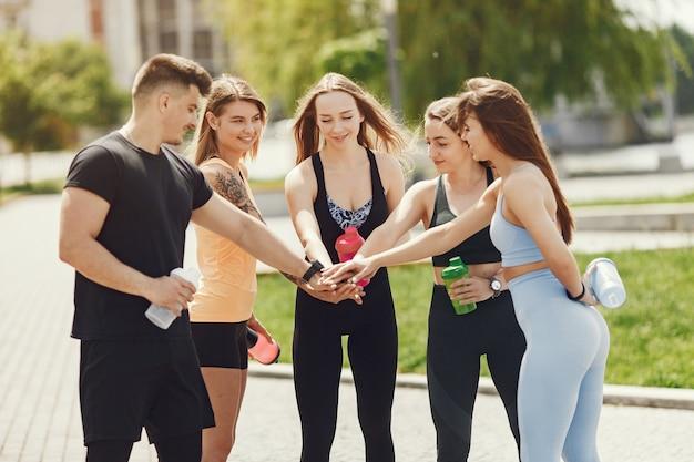 公園の人々のグループ。 4人の女の子を持つ男の子。水のボトルを持つスポーツの人々。