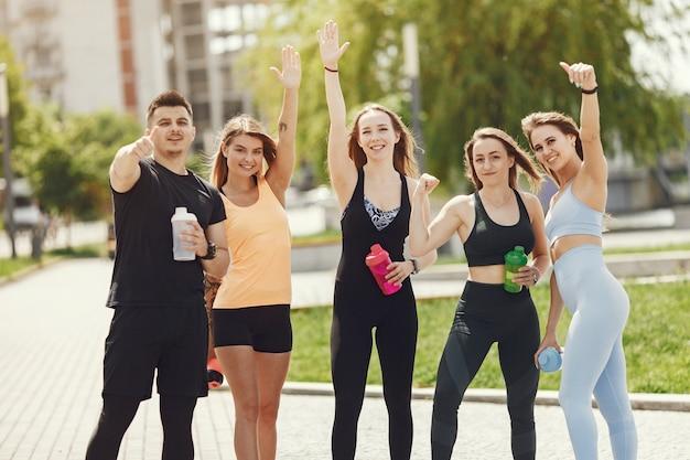Группа людей в парке. мальчик с четырьмя девочками. спортсмены с бутылками воды.