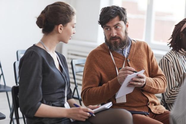 Группа людей в аудитории на бизнес-конференции фокусируется на бородатом мужчине, разговаривающем с женщиной, сидя на стульях