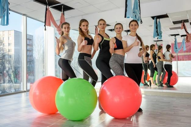 Группа людей в тренажерном зале, улыбаясь с мячом для пилатеса