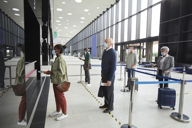 保護マスクを着用した人々のグループ列に並んでいる間、空港で社会的距離を保っている人々