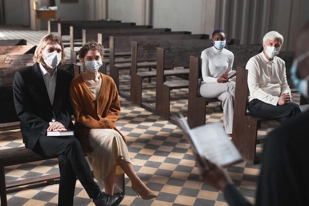 Группа людей в защитных масках сидит на скамейке и слушает мессу в церкви во время пандемии