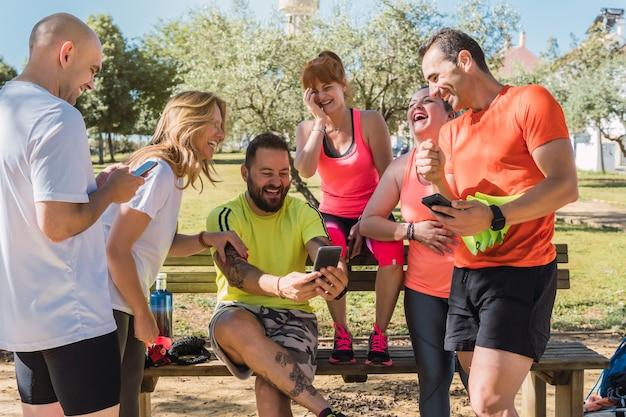 Группа людей в спортивной одежде смеется во время использования мобильного телефона в парке