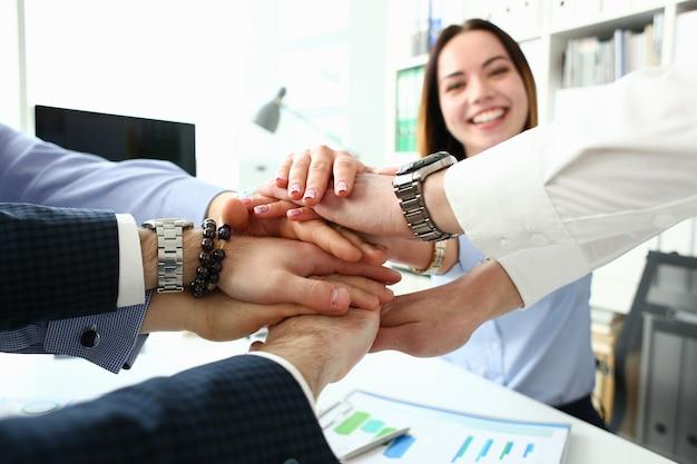 Группа людей в костюмах скрестила руки в куче для крупного плана победы. белый воротничок лидерство дай пять инициатив сотрудничества достижение корпоративный стиль жизни дружба деа, концепция кучи стека