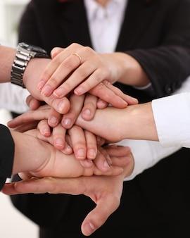 スーツを着た人々のグループは、勝利のクローズアップのために山積みで手を交差させました