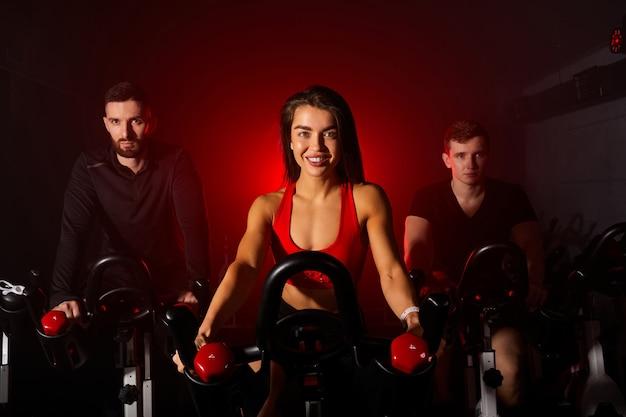 체육관에있는 사람들의 그룹, 심장 훈련을하고 다리 운동, 어두운 네온 조명이있는 연기가 자욱한 공간에서 체육관에서 회전 수업