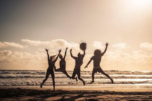 人々のグループは、背景に空とシルエットの体で日没時にビーチで一緒に幸せにジャンプします-友人のための夏休みの休日は、屋外のレジャー活動で楽しんでいます