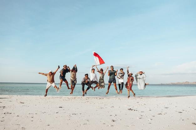 인도네시아 독립 기념일을 축하하기 위해 해변에서 함께 점프하는 사람들