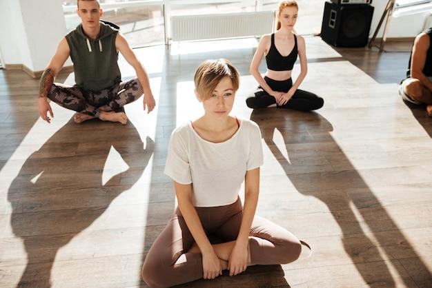 Группа людей, медитирующих и занимающихся йогой