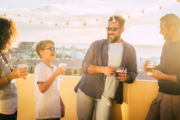 가족과 함께 혼합 된 연령대의 친구 그룹은 집에서 많이 마시고 웃고 함께 즐깁니다.