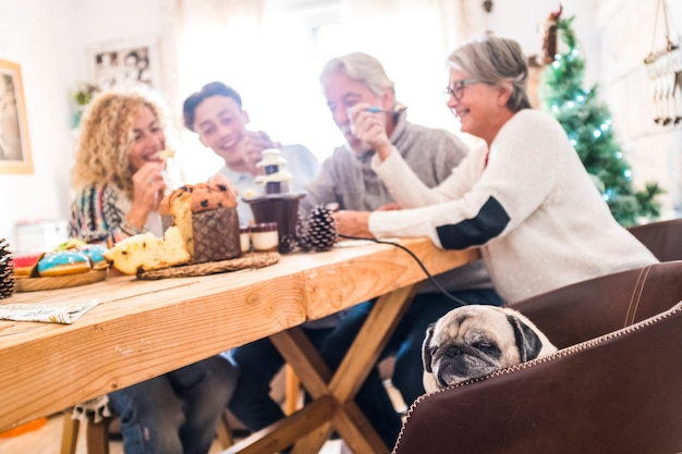 친구 나 백인 건방진 가족과 같은 혼합 연령대의 사람들 그룹은 크리스마스 축하 기간 동안 집에서 모두 함께 즐거운 시간을 보냅니다.