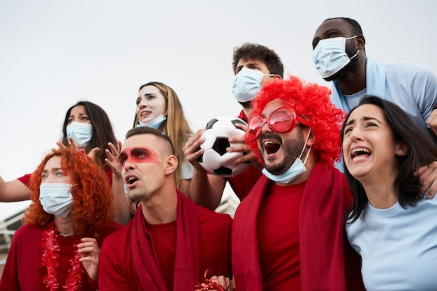 フェイスマックでサッカースタジアムでチームを応援するさまざまな人種の人々のグループ