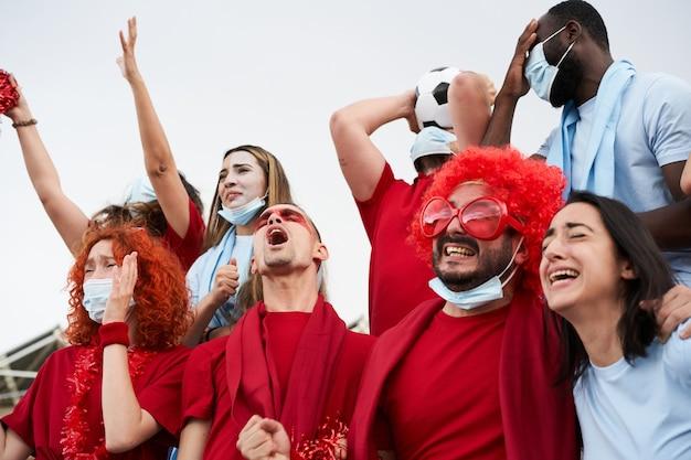 サッカースタジアムでチームを応援するさまざまな人種の人々のグループ