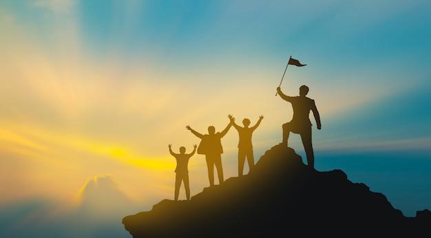 Группа людей на вершине горы в позе победителя. концепция совместной работы