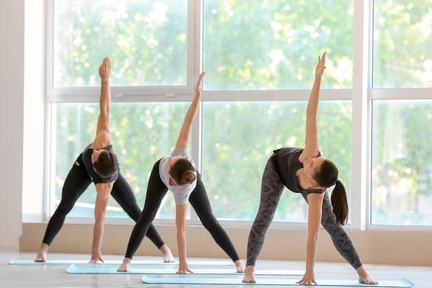 Группа людей, практикующих йогу в тренажерном зале