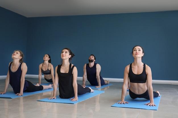 체육관에서 요가 연습하는 사람들의 그룹