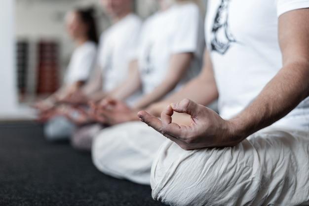 여러 사람들이 피트니스 스튜디오에서 긴장을 풀고 명상하고 스트레칭 운동을 합니다. 요가나 필라테스 훈련. 확대