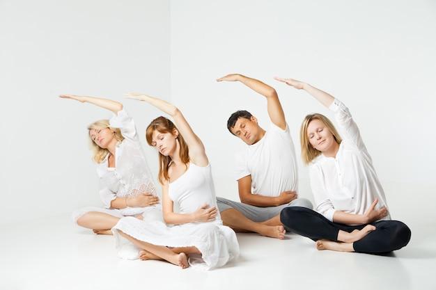 白いスタジオでリラックスしてヨガをしている人々のグループ