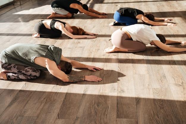 Группа людей, расслабляющих и практикующих йогу