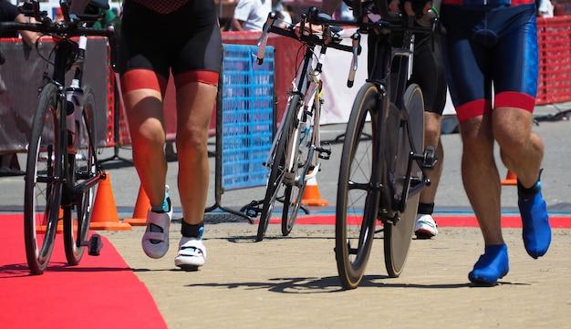 트라이애슬론 챔피언십에서 자전거를 탄 후 전환 지역으로 자전거를 타고 달리는 사람들