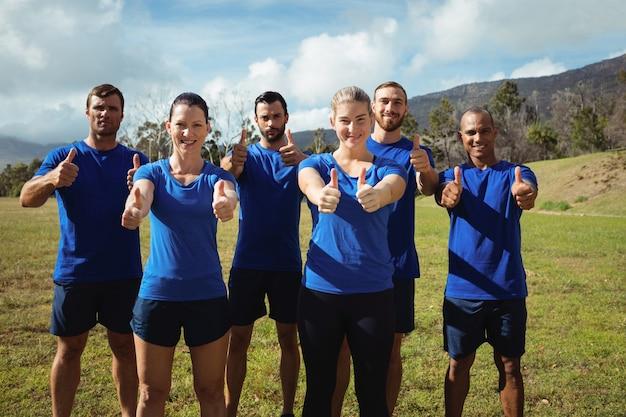 ブートキャンプのトレーニング中に親指を表示している人々のグループ