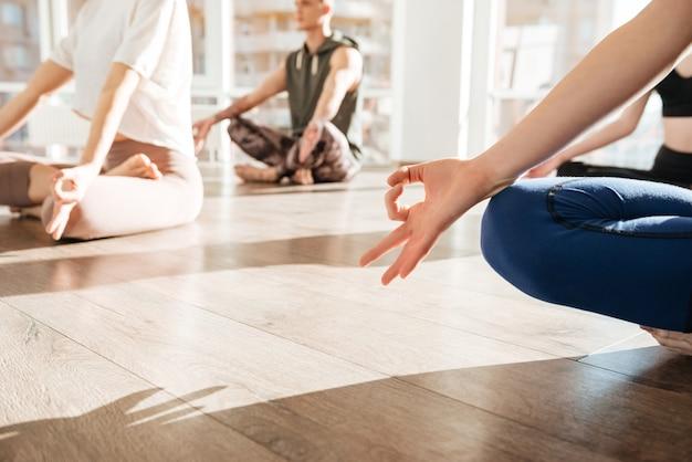 Группа людей, сидящих и медитирующих в студии йоги