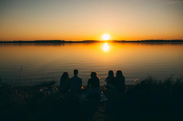 夕日の美しい景色を楽しみながら海のそばに座っている人々のグループ