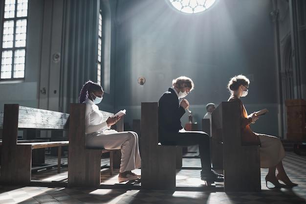 Группа людей, сидящих на скамейке и молящихся в старой красивой церкви